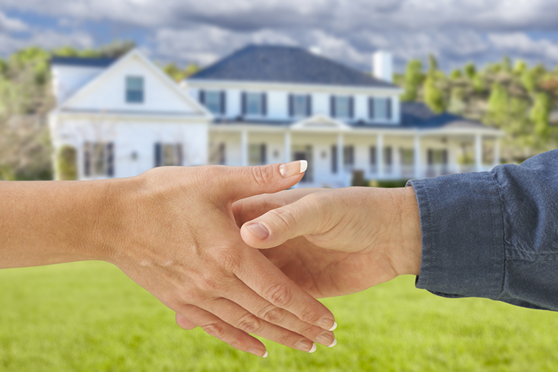Inspector and a Woman Shaking Hands in Front of a Beautiful New House before a home inspection