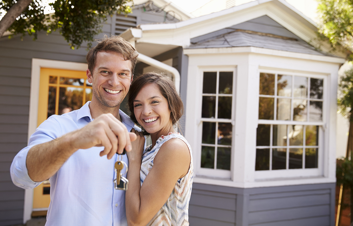 Couple With Keys Standing Outside New House After Home Inspection Services Were Provided