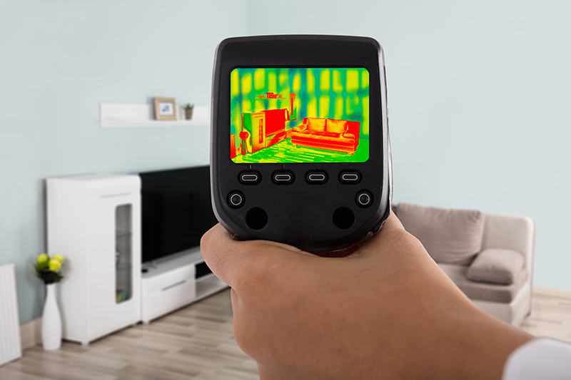 House Inspector Using An Infrared Thermal Camera In A Living Room During A Home Inspection